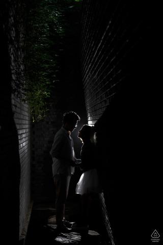 Galería de arte de ladrillo rojo Amor durante una sesión de retrato de compromiso bajo luces y sombras