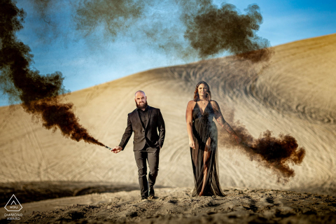 Sand Mountain, NV Smoke bombs in hand on sand dune during a pre-wed photoshoot in the desert