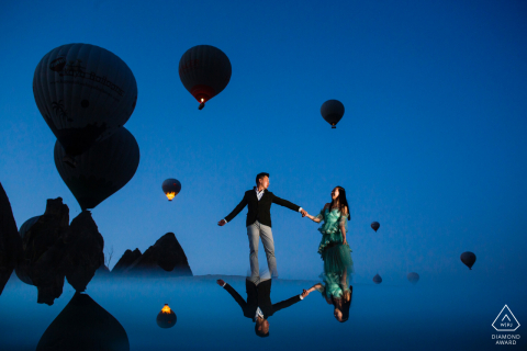 Cappadocia engagement photo session under a blue sky and hot air balloons