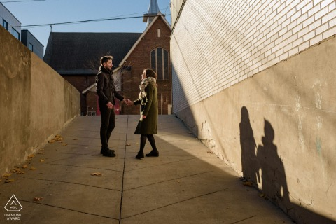 Verdun, Quebec Couple holding hands and dancing in an alleyway during pre-wed engagement photo shoot