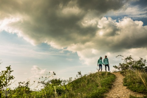 A Brno couple walk on the hill during a rural engagement shoot under the clouds