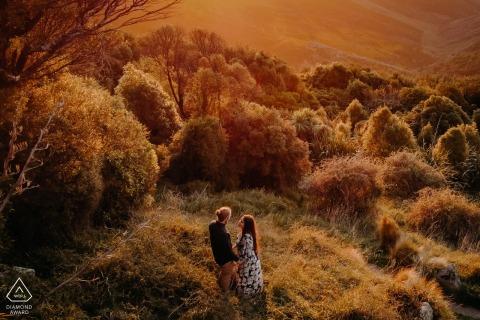 Port Hills Christchurch Nieuw-Zeeland buiten bos fotosessie met een koppel bij zonsondergang in de heuvels