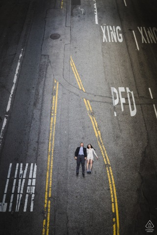 Downtown Los Angeles, California overhead urban photo shoot with the couple lying on the street between painted lines