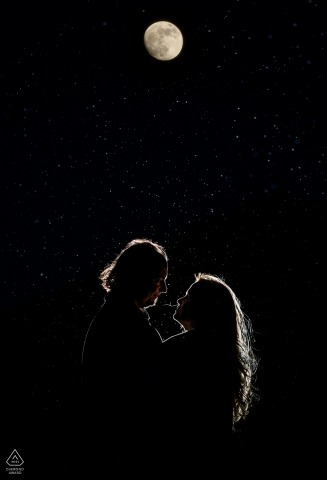 Rocky Mountain National Park mini backlit couple photo session before the wedding day created as The moon shows itself through the clouds of a snowy evening