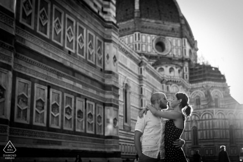 Piazza Duomo, Florence mini urban pic shoot before the wedding day while the couple is hugging in the sunlight by the buildings