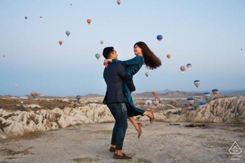 Cappadoce, Turquie Micro session de photo de montagne en plein air avant le jour du mariage avec un ascenseur ludique alors que les ballons décollent également