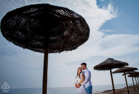 Aguilas, Spain mini beach couple photography session before the wedding day with some Love at the beach under the sun shade umbrellas