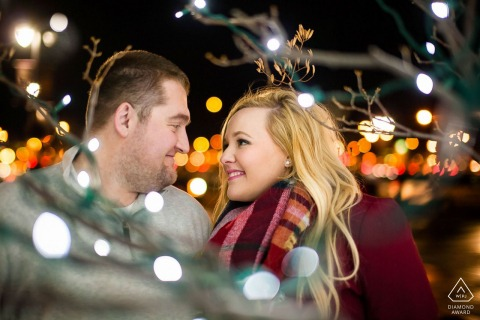 Fargo, North Dakota mini couple photo session before the wedding day with a look at each other as they are surrounded by Christmas lights at night