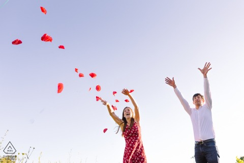 Montpellier, France outdoor portrait session under a clear sky with tossing flower petals overhead
