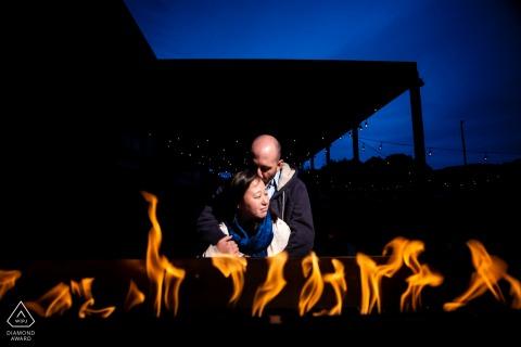 MN Night Brewery sesión de retrato previo a la boda con una pareja junto al fuego en una cervecería local.