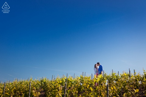 Champagne couple portrait in the vineyards under the big blue minimal sky