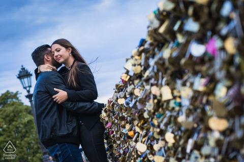 Retrato de pre boda al aire libre de París contra la enorme colección de candados cerrados