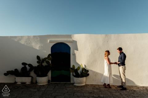 Retrato de pareja de Puglia en frente de un edificio de estuco blanco con cielo azul