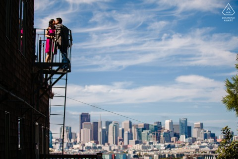 Potrero Hill, San Francisco city skyline couple portrait looking out over the city while standing on a fire escape stairway