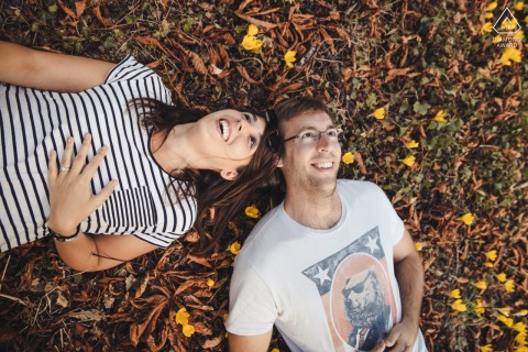 Gers playful couple photo shoot as they laugh laying in the grass