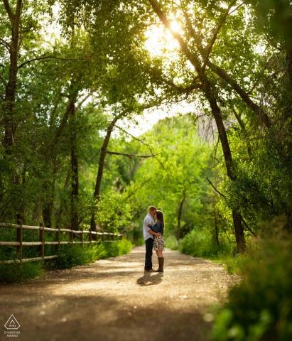 Clear Creek, Golden, Colorado sessione di fidanzamento pre matrimonio nella natura abbracciando il caldo sole estivo su questo sentiero verde