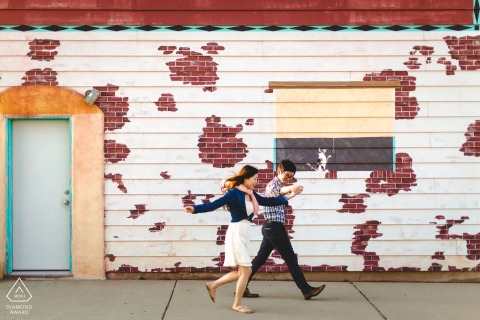 Peoria engagement shoot of couple taking an enthusiastic stroll in front of a fun mural