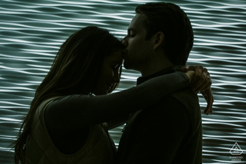 Chicago lighting studio indoor photo session with the couple before the wedding day with A kiss in front of a sculptural light wall