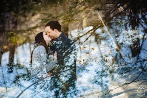 NH pre-wed retrato en el Madame Sherri Forest de una pareja que se inclina para un beso con el reflejo del cielo