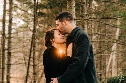 Stowe, VT verlobte Paarbildsession, die einen Stirnkuss mit leichtem Aufflackern aus dem Herzen zeigt
