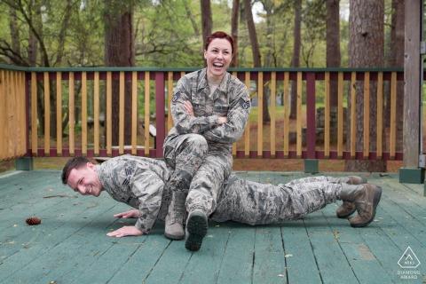 Pine Lake, GA pareja pre-matrimonio retrato mostrando un empuje hacia arriba con prometido uniformado militar sentado en la espalda