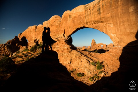 Arches National Park pre - wed image in Moab, Utah using A silhouette of the engaged couple at the window arches