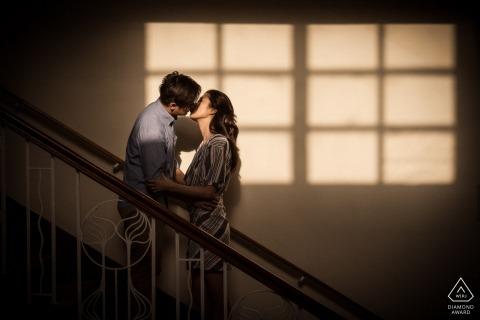 Hong Kong - image pré-mariage à l'intérieur avec des ombres de fenêtre sur le mur derrière le couple s'embrassant dans les escaliers