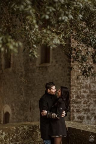 Retrato de pareja de Siena antes del matrimonio en Villa La Torre con paredes de piedra y árboles en lo alto