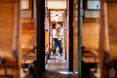 Trieste couple pre-wed portrait with Kiss in a historic train with lots of wood
