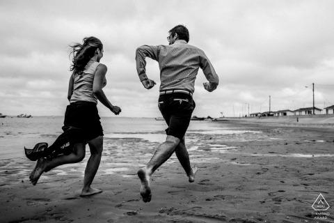 Imagen previa al matrimonio de Cap Ferret que muestra a dos amantes corriendo junto al mar en blanco y negro