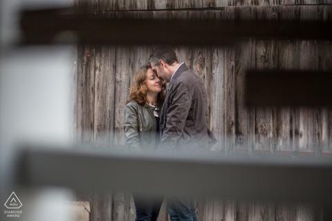 Cap Ferret sesión de fotos de compromiso de pareja con un dulce abrazo junto a la pared de la valla de madera rural