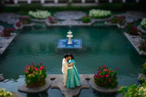 Udaipur paar verlovingsfoto sessie in Taj Lake Palace vanuit een hoge hoek boven de waterpoelen met planten