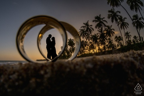 Maceio couple pre-wed portrait shot through the rings in the sand with some silhouettes