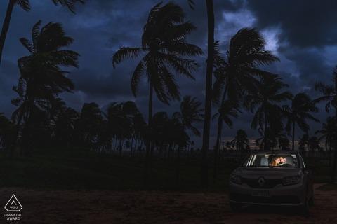 Maceio couple pre-wed portrait inside a lit car at dusk below the palm trees
