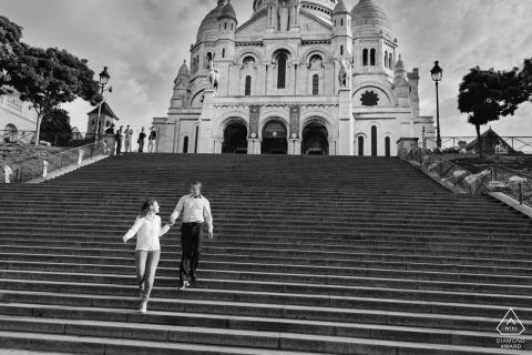 Paris Fine Art Pre Wedding Portrait en BW de una pareja caminando por un enorme tramo de escaleras debajo de una iglesia
