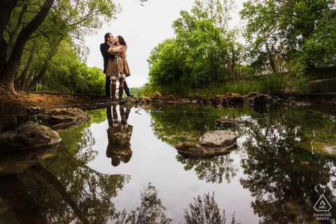 Foto de compromiso artístico de Tours en un jardín con el reflejo de la pareja en el agua del estanque