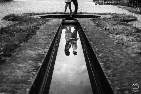 Imagen de compromiso de Bellas Artes de París en BW con una pareja reflejándose en la piscina de agua de la fuente