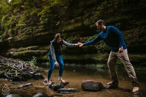 Starved Rock State Park Fine Art Engagement Image in Illinois as The couple is helping each other over a rocky stream while barefoot