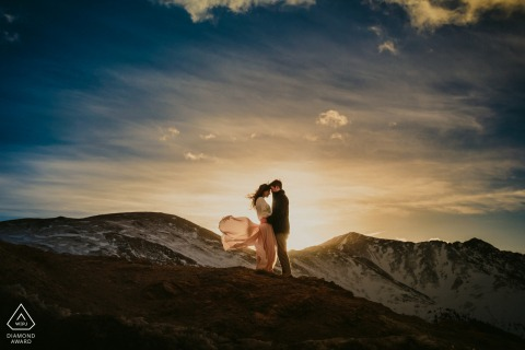 Loveland Pass, CO Pre Wedding Photoshoot in a Fine Art Style showing the couple Embracing in the cold wind during sunset
