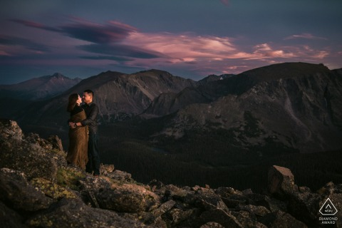 Rocky Mountain National Park Artful Engagement Picture of a couple staying warm together while watching the sunset at the top of a mountain range