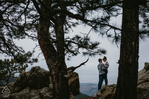 Boulder, CO Pre Wedding Photoshoot in a Fine Art Style for an Engaged couple embracing before a kiss through silhouetted pine trees
