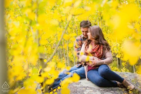 Rocky Wedding National Park Fotoshooting vor der Hochzeit in einem Kunststil für ein Colorado-Paar, das auf einem Felsen sitzt, der im Herbst von goldenen Espenblättern umgeben ist