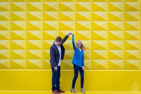 Denver Fine Art Engagement Session für ein Paar, das einen kleinen Tanz vor der bunten Wand in der Innenstadt macht