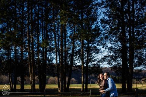 Tinicum Park Fine Art Engagement Image en el condado de Bucks, PA, bajo los árboles y el sol brillante