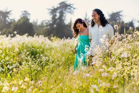 Fotografía de compromiso artístico de Santa Cruz que muestra a los amantes caminando por un campo de flores en un cálido y hermoso día de primavera