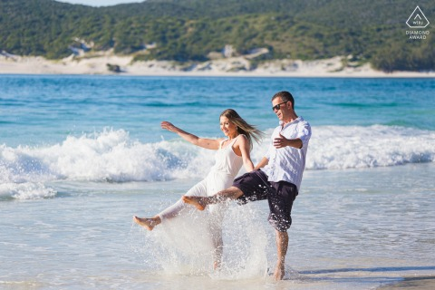 Arraial do Cabo, RJ environmental engagement e-session with the couple kicking up their feet in fun in the shallows by the shore