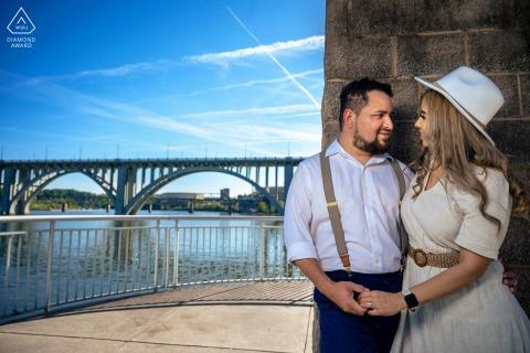 Volunteer Landing Park, Knoxville portrait e-session - homme tenant sa future épouse dans ses bras derrière une tour de pierre