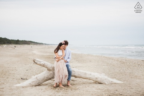 Sesión electrónica de retrato de Ravenna Wild Beach: pareja abrazada en un tronco entregado por el mar