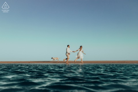 Maceió environmental engagement e-session of couple running, water, and a puppy