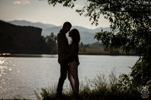 Laporte, Colorado environmental engagement e-session - a silhouette of a couple standing under a tree by a lake